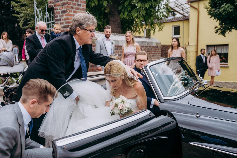 Hochzeitspaar eim Einsteigen in Hochzeitswagen