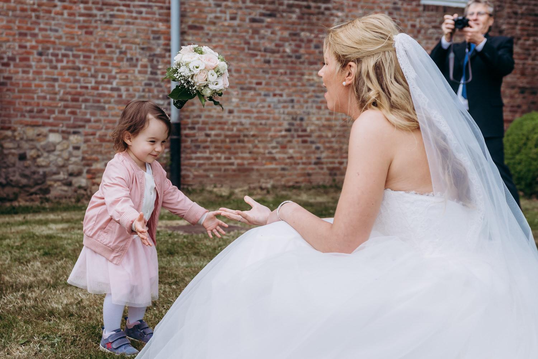 eine Braut im Spiel mit einem kleinem Mädchen