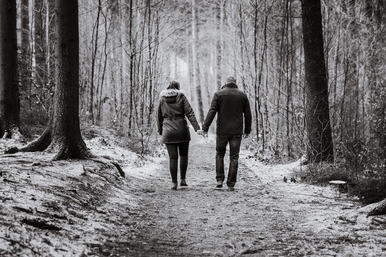 Paar beim Spaziergang durch den Wald im Winter