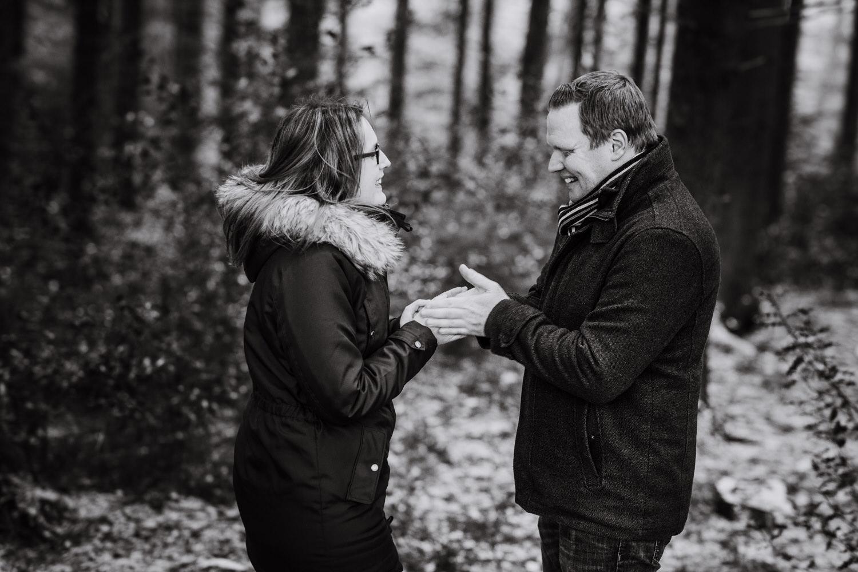 Paar hat kalte Hände bei einem Paarshooting. Er wärmt ihre Hände