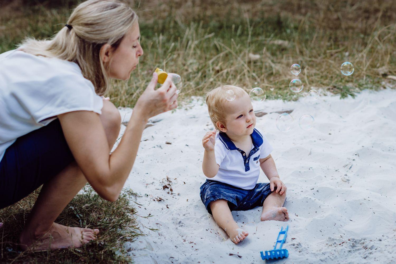 Kind und Mutter spielen mit Seifenblasen