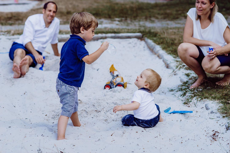Kinder spielen mit Seifenblasen beim Familienshooting