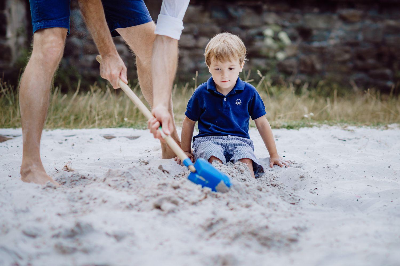 Spiele im Sandkasten mit Vater und Sohn
